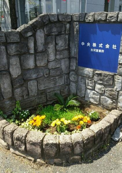 古河営業所入り口の看板と花壇